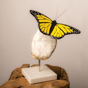 Glazen beeld vlinder van zwart geel glas geplaatst op een sokkel van wit marmer